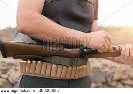 Close Up Of An Unrecognizable Hunter, Loading Shotgun, Holds A Shotgun And Ammunition In His Hand. H