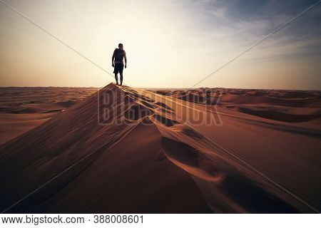Desert Adventure. Young Man Walking On Sand Dune Against Sunset. Abu Dhabi, United Arab Emirates