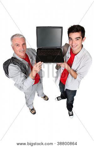 Two men showing a laptop computer