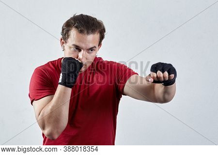 Young Man Boxes, Making Jab With Left Hand. Black Bandages, Red T-shirt, Determined Face Expression,