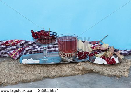On A Blue Background, On A Tray, There Is A Glass Of Tea With Viburnum And A Bowl With Viburnum Berr