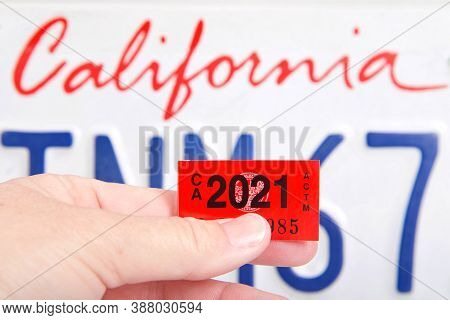 Alameda, Ca - Oct 01, 2020: Close Up Of Hand Holding California Dmv Tags With Ca License Plate In Ba