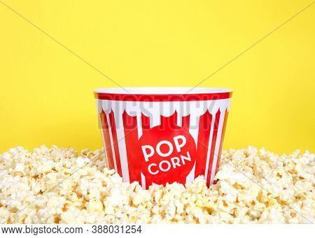 Close Up Of A Red And White Striped Popcorn Bucket Surrounded By Freshly Popped Popcorn, Bright Yell