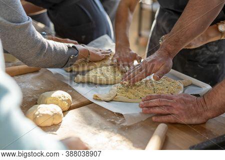 Culinary Master Class. Closeup Of People Hands Preparing Khachapuri. Traditional Georgian Cheese Bre