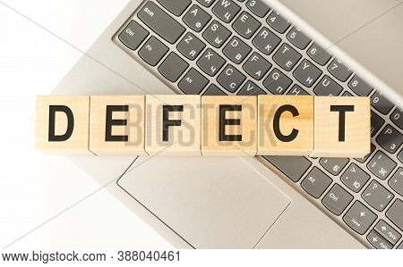 Word Defect. Wooden Cubes With Letters Isolated On A Laptop Keyboard. Business Concept Image.