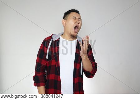 Sleepy Tired Funny Young Asian Man Yawning, Half Body Portrait Over Grey Background