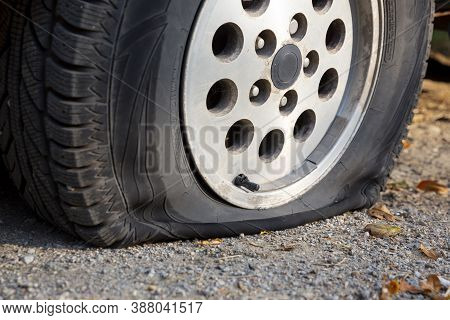 A Car With A Flat Tire Is Seen Parked On A Dirt Road.