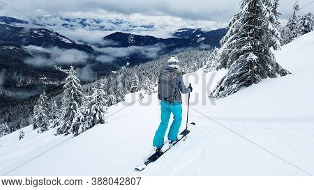 Young Skier Stands On A Gravelly Slope With Her Skis. The Mountain Slopes Are Covered With Snow. Pin