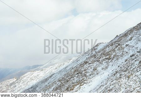 Snow Covers Rocky Mountain Slopes, Which Rise Up Into A Sky Filed With White Couds. Patches Of Sunsh
