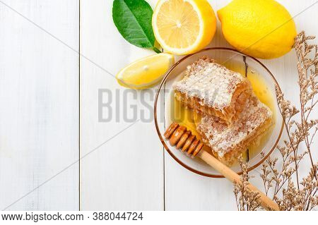 Honeycomb On Dish With Honey Dipper With Lemons On White Wood Background, Bee Products By Organic Na