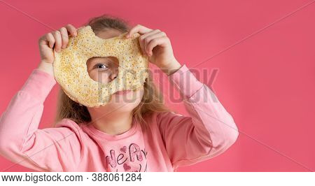 Little Cute Girl Holds A Pancake And Looks Through A Hole In It, On A Pink Background. Sweet Breakfa