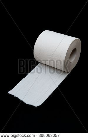 Single Roll Of Unrolled White Toilet Paper. Isolated On Black Background. Close-up. Copy Space. Vert