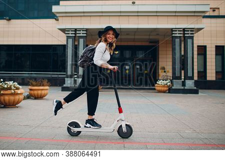Young Woman With Electric Scooter At The City