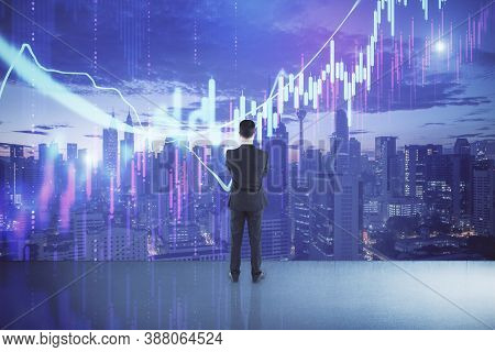 Thoughtful Businessman Standing In Abstract Office Interior With Glowing Forex Chart And Night City