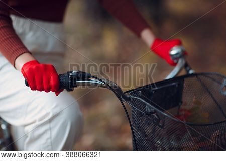 Young Woman Riding Bicycle In Red Gloves And Face Mask At Autumn Park