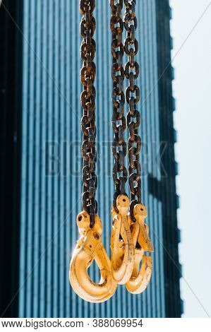 The Hooks Of The Mobile Crane Near The Glass Of High Buildings.lots Of Hooks Hanging From Chains Sus