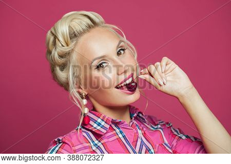 Pin-up Woman Biting Cherry On Vibrant Pink
