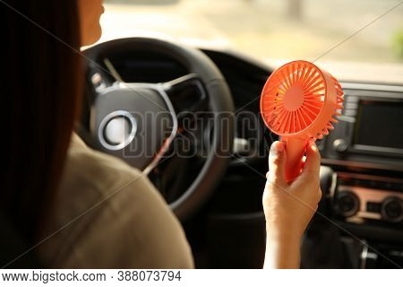 Woman With Portable Fan In Car On Hot Summer Day, Closeup