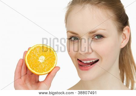 Woman holding an orange while placing her tongue on her lips against white background