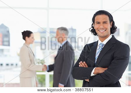 Young smiling executive standing upright in a suit with business people behind him