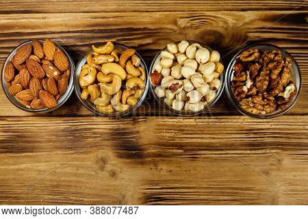 Assortment Of Nuts On Wooden Table. Almond, Hazelnut, Walnut And Cashew In Glass Bowls. Top View, Co