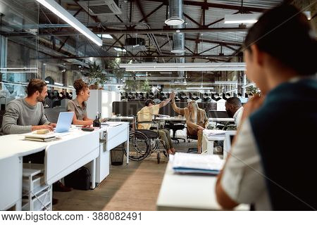 Portrait Of Mixed Race Business Team Working In Office. Young Co-workers In Casual Wear Give High-fi