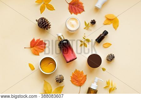 Autumn Skin Care Products And Autumn Leaves On Yellow Background, Flat Lay, Copy Space.  Seasonal Be