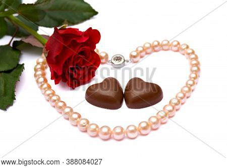 Valentine's Composition With Red Rose, Chocolaty Candy And Pearl Necklace On White Background With S