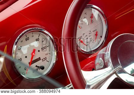 Steering Wheel With Crome Beams, Speedometer, Fuel, Oil, Water, Volts Dials On Front Panel Of Red Ol
