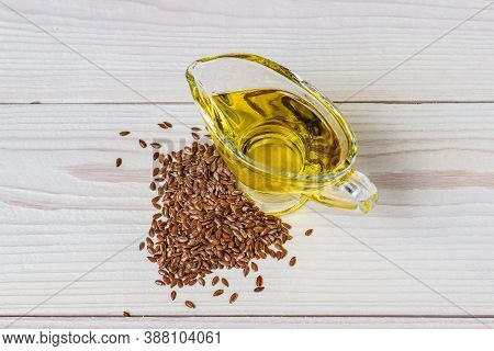 Flaxseed Oil In A Glass Gravy Boat. Flax Seeds On A White Background