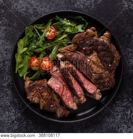 Grilled Beef Steak With Spices On A Black Plate, Top View.