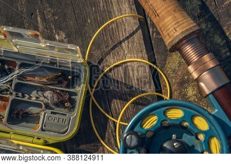 Fly Fishing Rod With On Wood Background. Fly Fishing Gear, Which Includes A Reel And Containers Of F