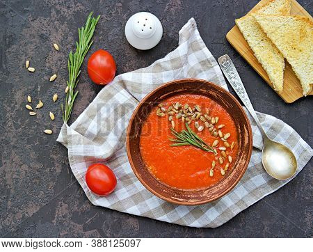 Cream Soup Of Baked Sweet Pepper And Tomato In A Clay Bowl On A Brown Concrete Background. Served Wi