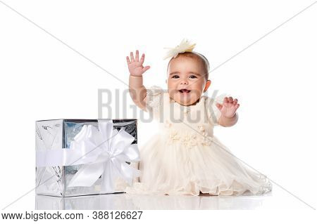 Happy Smiling Baby Girl Wearing Beautiful Festive Dress And Headband With Bow Sitting On White Studi
