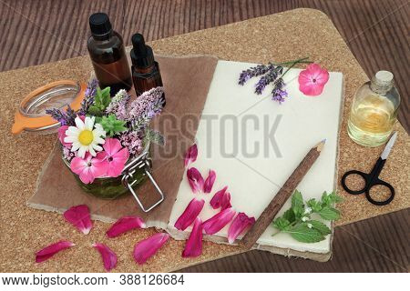Natural herbal medicine preparation with flowers and herbs steeping in a jar with oil & loose for aromatherapy essential oil with tincture bottles and hemp notebook. Naturopathic health care concept.