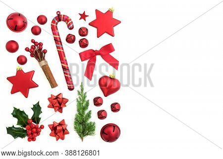 Christmas symbols with red bauble decorations, bows, winter holly, fir & cinnamon on white background with copy space for text. Xmas composition for the holiday season. Flat lay, top view.