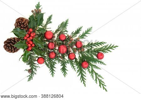 Christmas decorative arrangement with winter holly, pine cones, cedar cypress & red bauble decorations on white background. Festive themed element. Flat lay, top view, copy space.