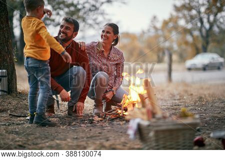 Happy mom and dad camping with peschool son; Quality family time concept