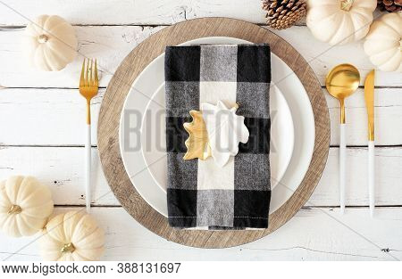 Autumn Harvest Or Thanksgiving Dinner Table Setting With Plates, Flatware, Buffalo Plaid Napkin, Pum