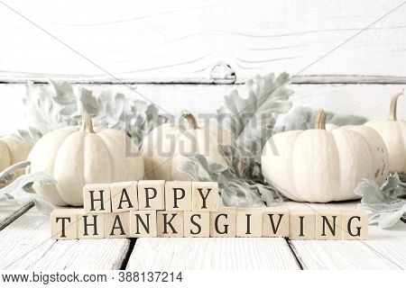 Happy Thanksgiving Greeting On Wooden Blocks Against A White Wood Background With White Pumpkins And