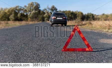 Red Warning Triangle On The Road In Front Of A Broken Car. Breakdown Of The Car In Sunny Weather. Sa