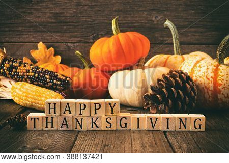 Happy Thanksgiving Greeting On Wooden Blocks Against A Rustic Wood Background With Pumpkins And Autu