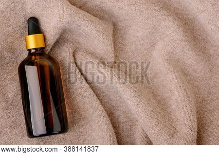 Essential Natural Oil In Dark Glass Bottle On Knitted Background Flat Lay. Beauty Cosmetic Product F