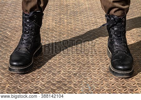 Legs Of A Man In Berets. On The Metal Floor. Symbol: Aggressor. Cockiness. Military Style