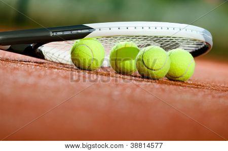 Close up of tennis racquet and balls on the clay tennis court