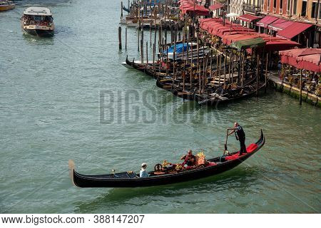 Venice, Italy, October 23 2019: Venice Cityscape With Grand Canal Waterway, And Gondolier On Gondola