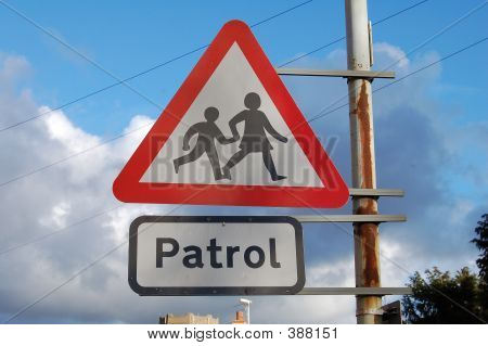 School Crossing Patrol Sign Attached To A Rusty Pole With A Blue Sky Background.