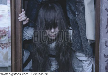 Mad Scary Girl In Cupboard At Dark Night. Horror Background With Child Possessed By Devil. Demon Pos