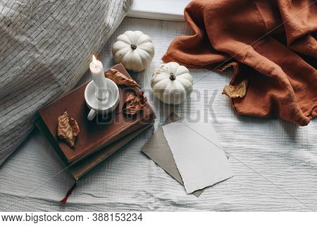 Autumn Still Life. Burning Candle, Books And Linen Pillow Near Window. Blank Greeting Card Mockup Sc