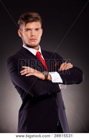 portrait of a young business man looking serious into the camera, with his arms crossed, over dark background